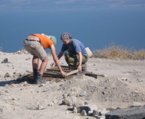 Two archaeological excavators look for artifacts by sifting soil from a church in the mountaintop  Decapolis city of Hippos in 2006. In the background is the Sea of Galilee.Photos by Marc Hequet