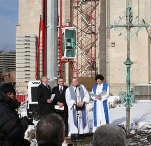 Before raising the cross onto the spire at Central Lutheran Church, Minneapolis, a blessing ceremony is held. From left, participants include Franklin Dietrich, Central's fiscal and property committee; Bill Masche, congregation president; the Rev. Richard A. Nelson, senior pastor; and the Rev. Kristen Jacobson, associate pastor. Photo: Joe Bjordal.
