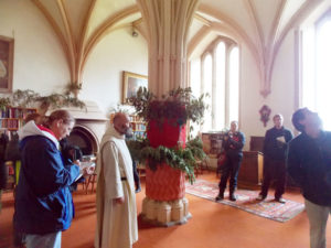 Father Giles, a monk at Pluscarden Abbey, shows the Chapter Room to Augsburg College students (left to right) Julie Fedeler, Amber Kalina, Matt Current, and John West. The Chapter Room is basically where the monks meet, so-called because a chapter from the Rule of Saint Benedict is read at the start of each meeting.